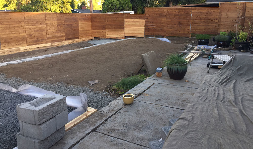 Photo of our half-finished backyard landscaping project. Unfinished retaining wall, materials left everywhere and dirt with no grass or mulch